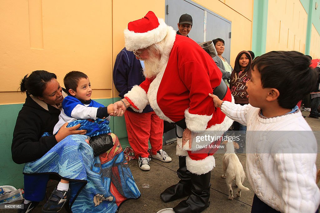 Santa Claus greets children as people stand in line for hours to receive gifts of food, personal care and household items and toys at the Miracle in South Central event, part of the nationwide Miracle on Main Street, USA program to help working poor and disadvantaged families, on December 13, 2008 in the South Central neighborhoods of Los Angeles, California. About 5,000 families are expected to receive enough food at the event to supplement meals for a family of four for a week. Miracle on Main Street, USA is sponsored by The National Basketball Players Association (NBPA) along with Feed The Children, Feed 333, Humanity Unites Brilliance (HUB) and hosted by the Salvation Army.