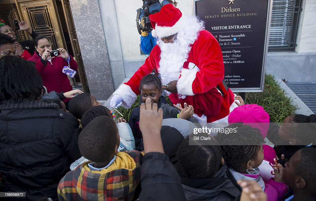Santa Claus hands out candy canes to students from Savoy Elementary School as he arrives for the U.S. Capitol Police's 13th Annual Holiday Party in the Dirksen Senate Office Building on Wednesday, Dec. 19, 2012.