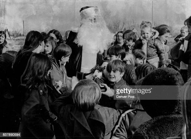 Santa Claus Has Come To Town Santa Claus is greeted by children Friday after arriving by helicopter to celebrate the Christmas holidays with 100...
