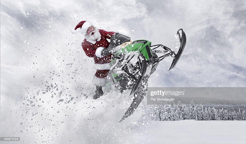 Santa Claus having fun with his snowmobile : Stock Photo