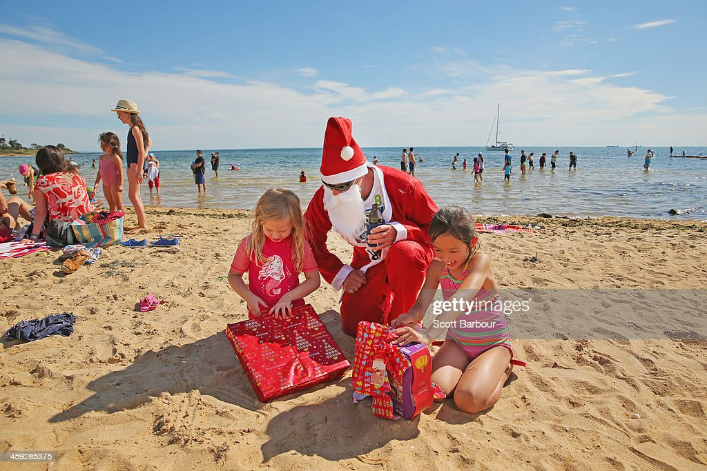 Santa Claus helps children to open their Christmas presents on Christmas Day at Brighton Beach on December 25, 2013 in Melbourne, Australia. Brighton Beach features 82 colourful bathing boxes, which are one of the tourist icons of Melbourne. Temperatures in Melbourne on Christmas Day topped thirty degrees celcius.