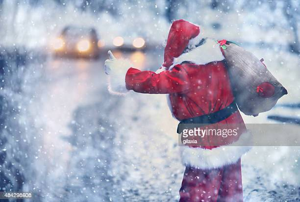 Santa Claus hitchhiking on a snowy day.