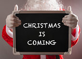 Santa Claus holding a black chalk board written with CHRISTMAS IS COMING