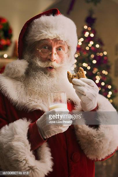 Santa Claus holding biscuit and glass of milk, portrait, close-up
