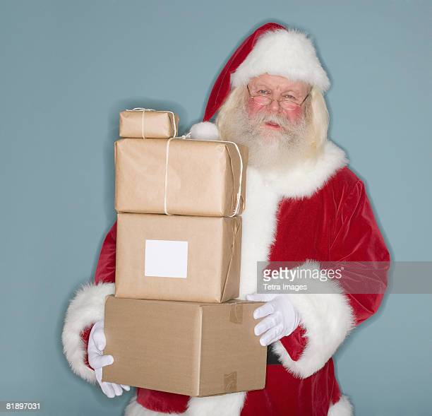 Santa Claus holding stack of packages