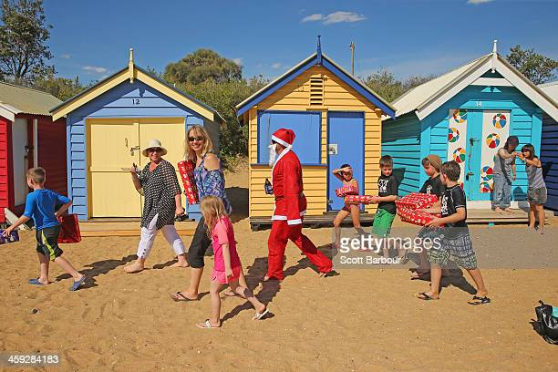 Santa Claus holds a beer as he walks with children holding their Christmas presents on Christmas Day at Brighton Beach on December 25 2013 in...