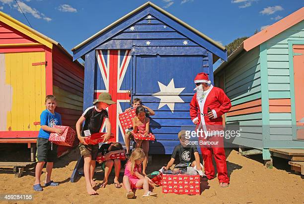 Santa Claus holds a beer as he watches children open their Christmas presents on Christmas Day at Brighton Beach on December 25 2013 in Melbourne...