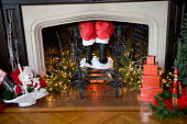 Santa's pants and boots coming down the chimney with Christmas decorations around