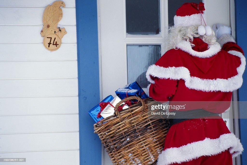 Santa Claus knocking door, rear view