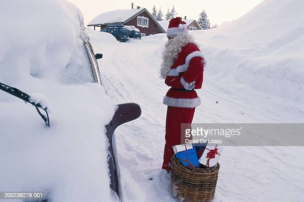 Santa Claus looking at car, with gifts