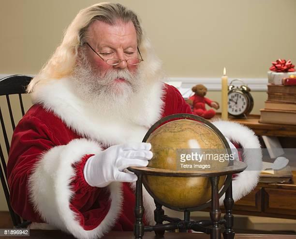 Santa Claus looking at globe