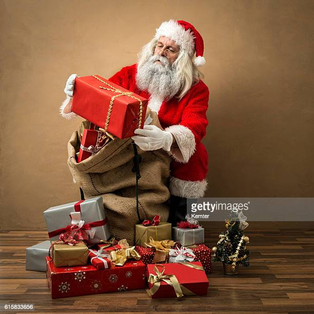 santa claus looking at present in his hands