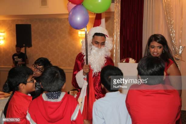 Santa Claus makes a brief appearance during the V Rambaikulam Girls Maha Vidyalayam Old Students Association Christmas gala celebration in Toronto...