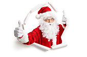 Santa Claus making thumbs up through a paper hole isolated on white background