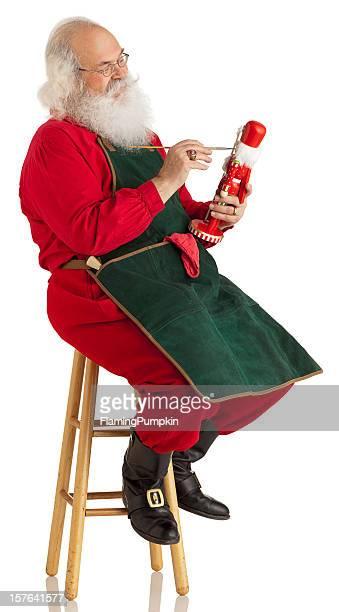 Santa Claus making toys on a White. Vertical. XL