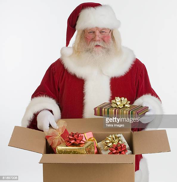Santa Claus packing gifts in box