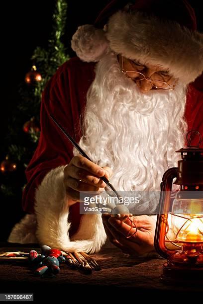 Santa Claus peinture un jouet