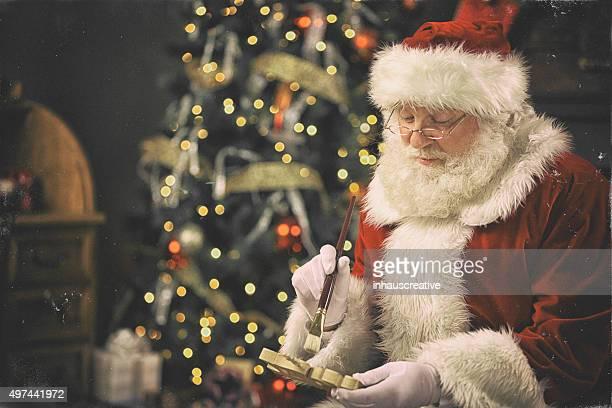 Santa Claus pintura un juguete