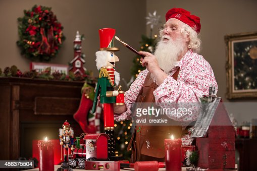 Santa Claus Painting Nutcracker In Toy Shop Stock Photo