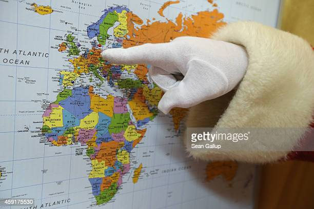 Santa Claus points to the approximate location of the Christmas post office on a map on November 18 2014 in Himmelpfort Germany Every Christmas...