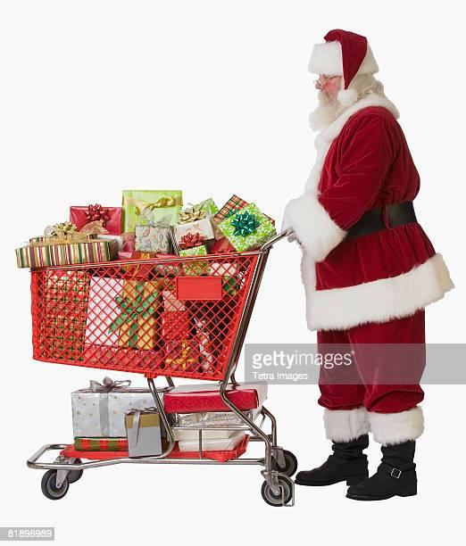 Santa Claus pushing shopping cart full of gifts
