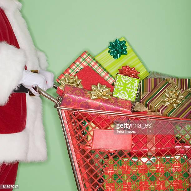 Santa Claus pushing shopping cart of gifts