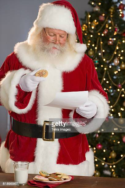 Santa Claus reading letter and eating cookies