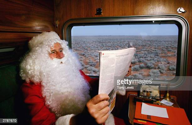 Santa Claus reads a newspaper as the Nullarbor Plain rolls past his train window December 5 2003 in outback Australia The Nullarbor is an 770 km wide...