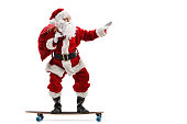 Full length profile shot of Santa Claus riding a longboard isolated on white background