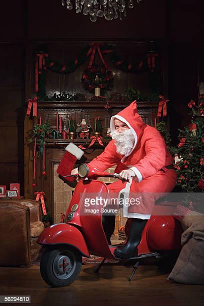 Santa Claus riding a moped