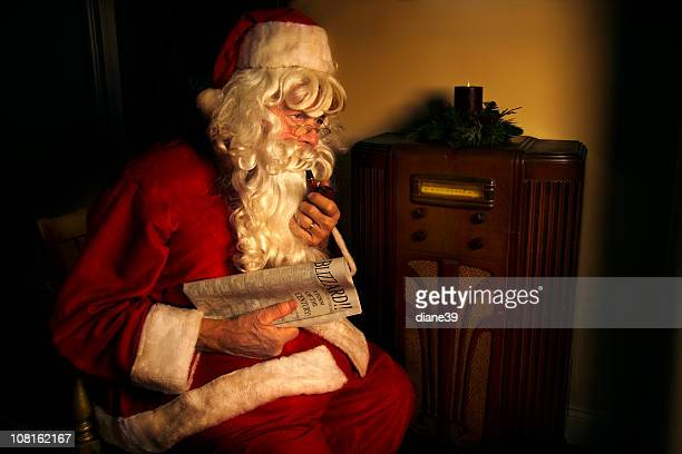 Santa Claus Sitting by Antique Radio and Holding Newspaper