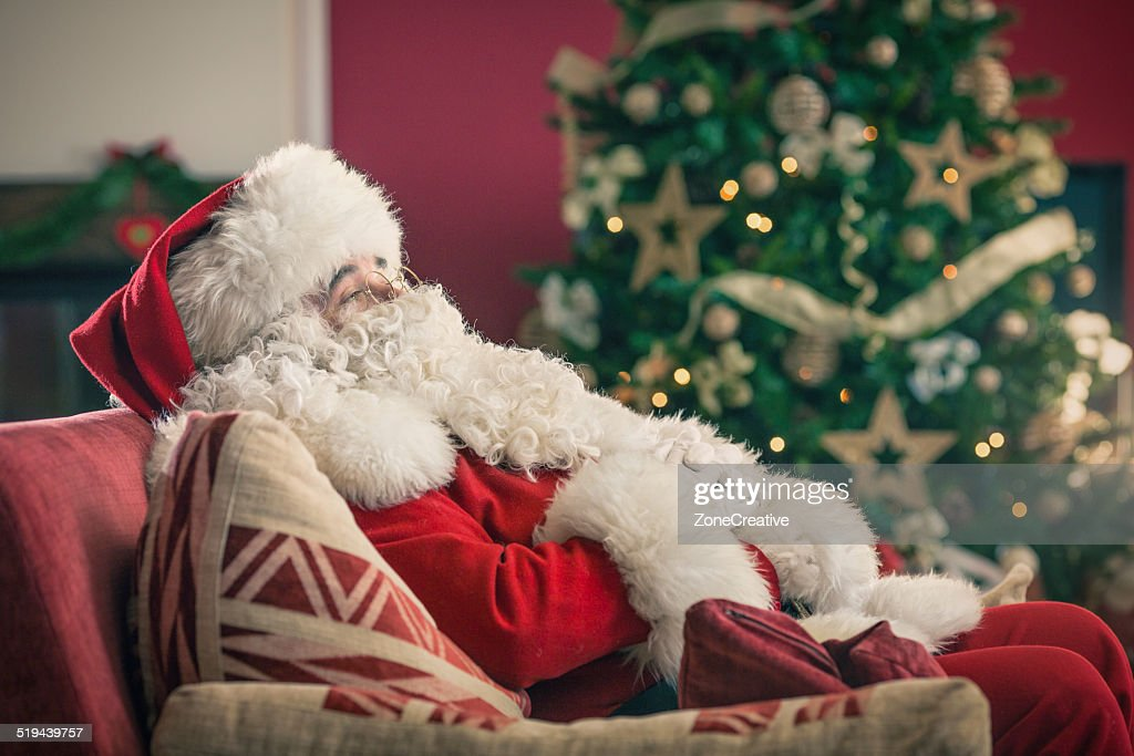 Santa claus sitting on a red couch stock photo getty images