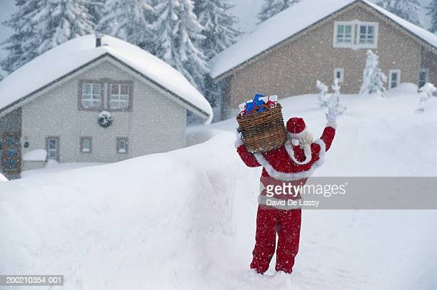 Santa Claus standing with basket of gifts