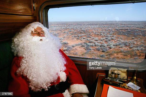 Santa Claus takes a nap as the Nullarbor Plain rolls past his train window December 5 2003 in outback Australia The Nullarbor is an 800 kmwide...
