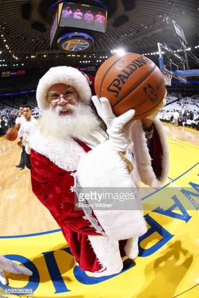 Santa Claus takes a picture before the Los Angeles Clippers plays the Golden State Warriors on December 25 2013 at Oracle Arena in Oakland California...