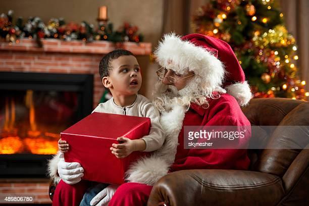 Babbo Natale parlando di piccolo ragazzo afro-americano a casa.