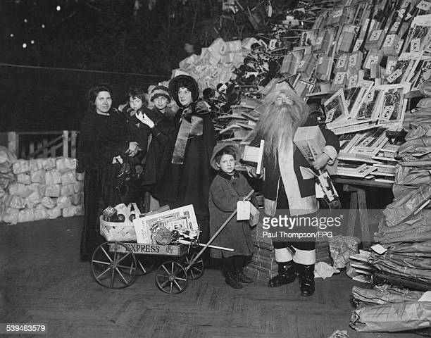 Santa Claus visits the 9th Regiment Armory on 14th Street New York City to distribute toys to children circa 1910 Evangeline Booth Commander of the...