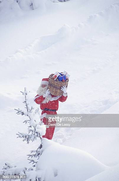 Santa Claus walking in snow with basket, elevated view