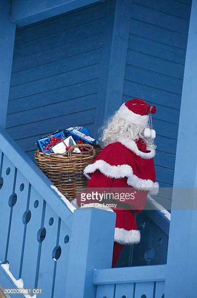 Santa Claus walking on stairs of house with gifts