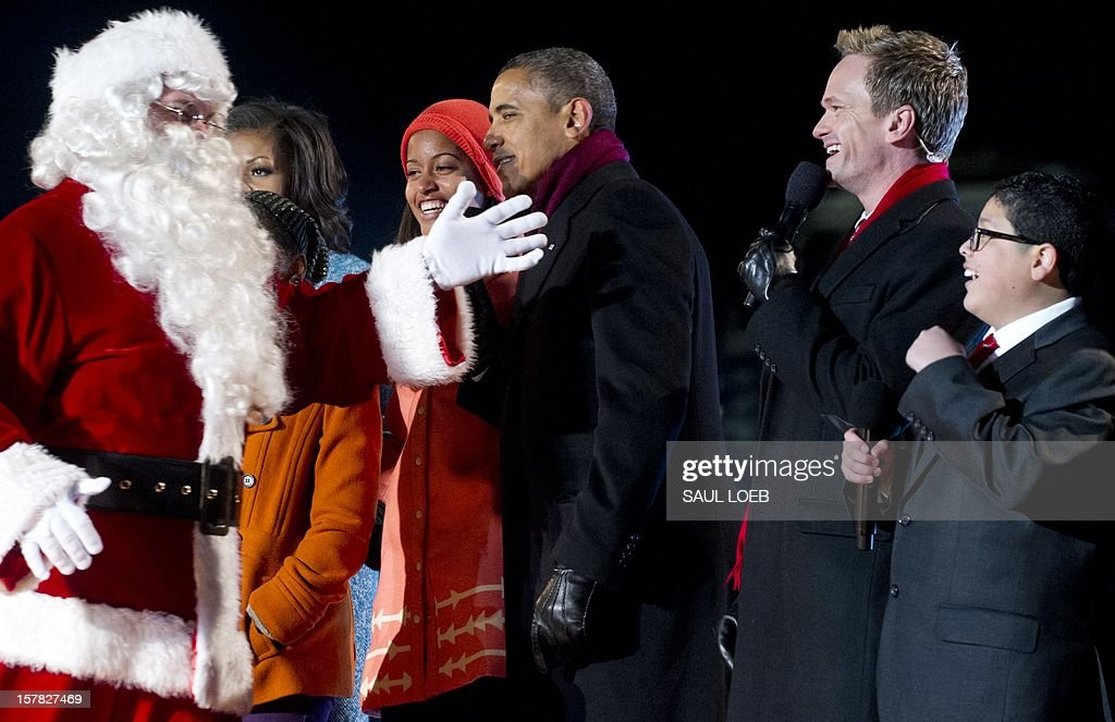 Santa Claus walks past US President Barack Obama (C) and his daughter Malia as they sing with actor Neil Patrick Harris (2nd R) and actor Rico Rodriguez (R) from the televison show 'Modern Family' during the National Christmas Tree Lighting on the Ellipse adjacent to the White House in Washington, DC, on December 6, 2012. The annual event, hosted by Harris, features US President Barack Obama and performances by Jason Mraz, Ledisi, James Taylor, Kenny 'Babyface' Edmonds, Colbie Caillat and American Idol season 11 winner Phillip Phillips. AFP PHOTO / Saul LOEB