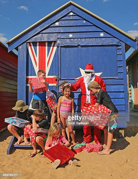 Santa Claus watches children open their Christmas presents on Christmas Day at Brighton Beach on December 25 2013 in Melbourne Australia Brighton...
