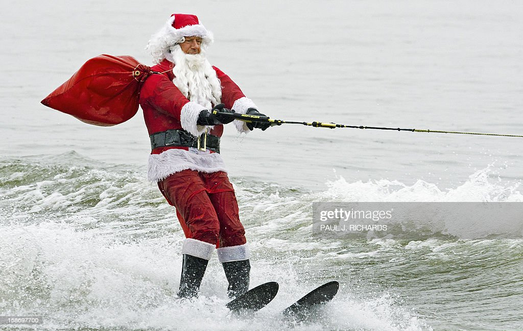 Santa Claus water-skis on Potomac River near Washington, DC, December 24, 2012, at National Harbor in Maryland during th 27th Annual Water Skiing show. This unusual annual event features a water-skiing Santa, flying elves, the Jet-skiing Grinch, and Frosty the Snowman performing on the Potomac River. AFP PHOTO/Paul J. Richards