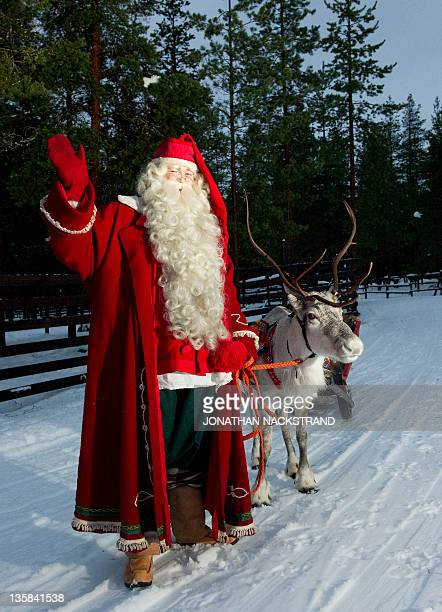 Santa Claus waves as he stands with a reindeer and sled outside Rovaniemi Finnish Lapland on December 15 2011 AFP PHOTO/JONATHAN NACKSTRAND