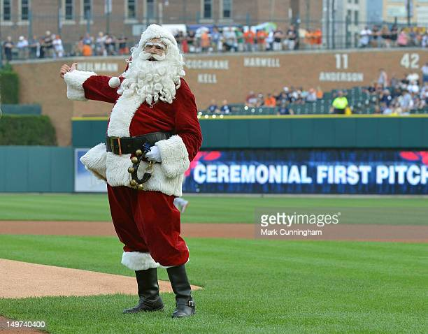 Santa Claus waves to the crowd before the ceremonial first pitch prior to the 'Christmas in July' promotion game between the Los Angeles Angels of...