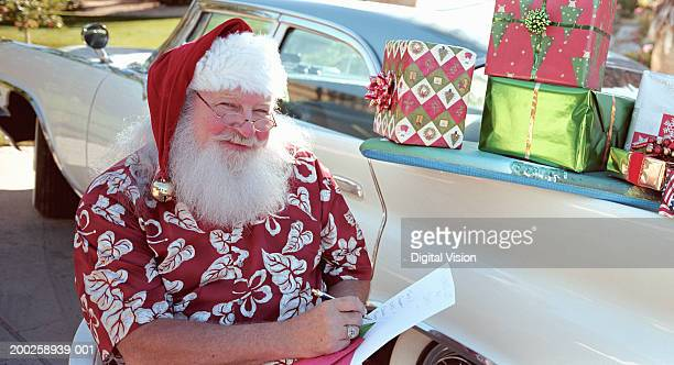 Santa Claus wearing printed shirt, presents stacked on side of car
