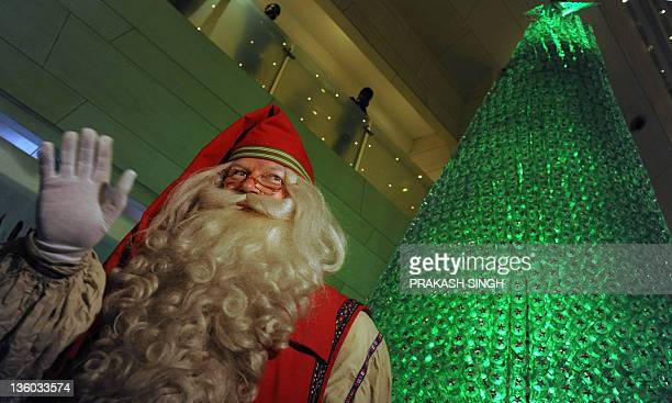 Santa Claus who travelled to India from Finnish Lapland waves to well wishers during preChristmas celebrations at a hotel in New Delhi on December 17...
