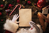 Christmas background, Santa Claus writting on blank paper sheet over wooden table with copy space