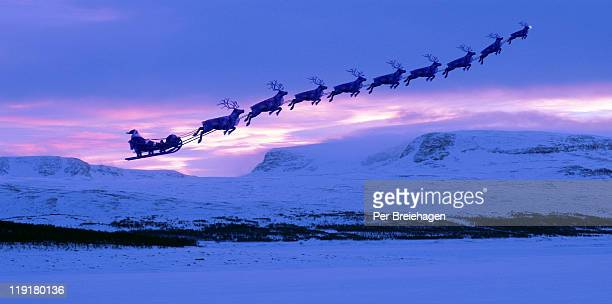 Santa Clause and reindeer flying into the sunset