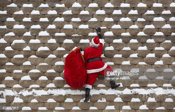 Santa climbs a snowy wall