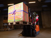 Santa driving forklift carrying big present in warehouse